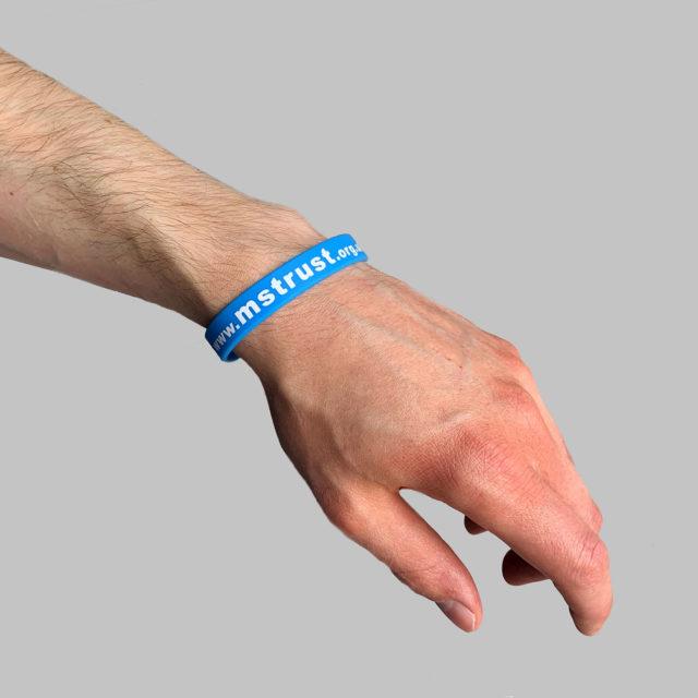 Blue MS Trust wristband on a male's wrist